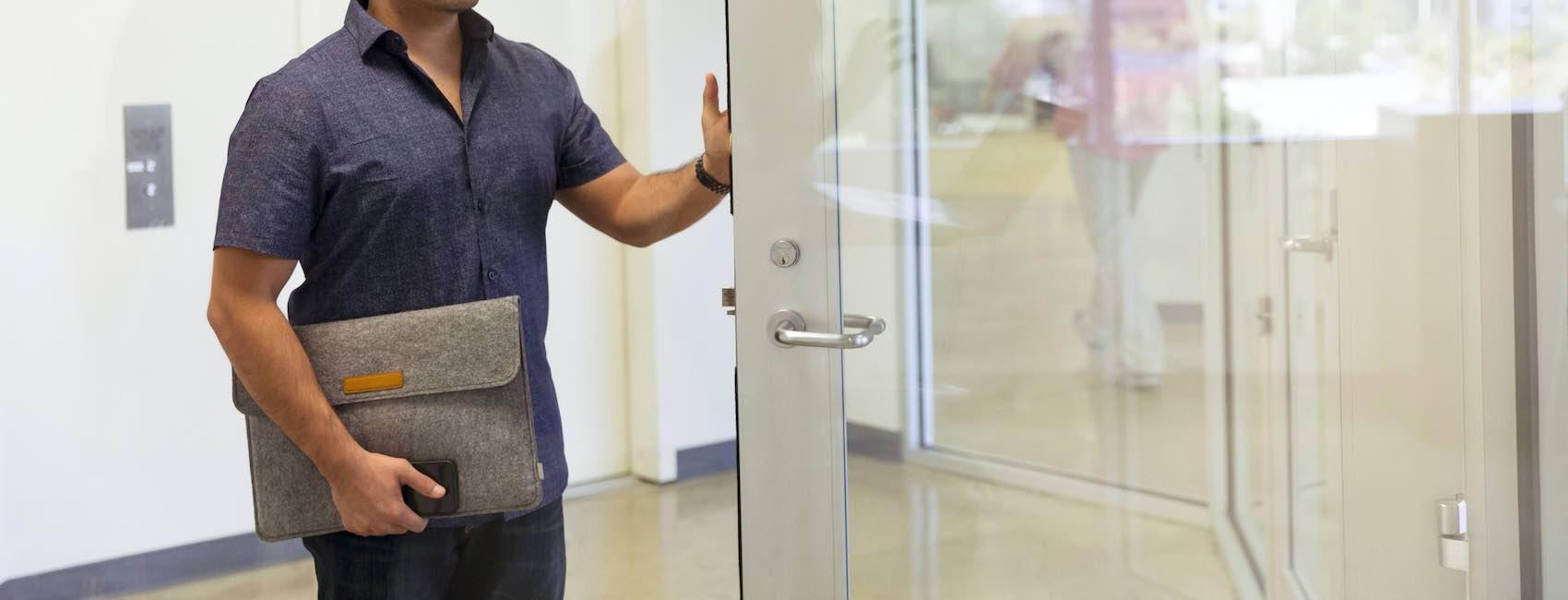 Man walking out office door